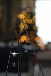Candle holder with light in the christmastree as bokeh in blurred background.