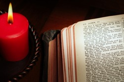 Candle illuminating page from Bible highlighting the resurrection