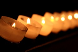candle in a line in a church, with shining light