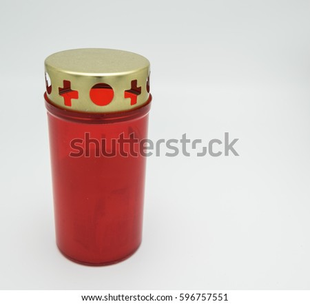 candle in a red plastic holder with golden metallic cape