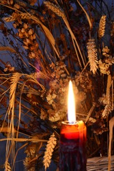 Candle in a vintage old wine bottle with dried flowers background composition.