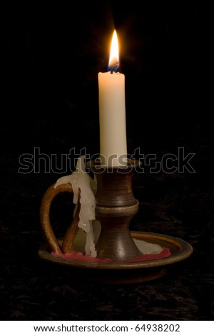 Candle in old fashioned candlestick holder on black background
