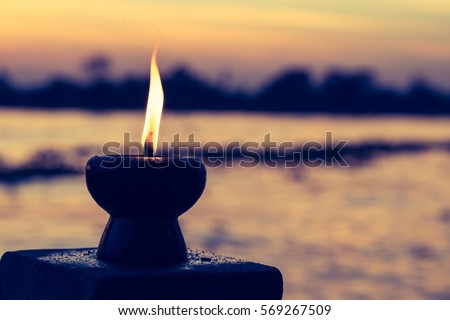 Candle light fire lamp nearby abstract background river during sunset or sunrise in countryside. Melting candlestick in evening twilight. Religion abstract concept.Earth hour 2018