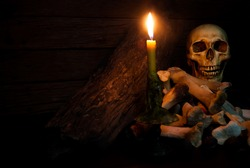 Candle lighting of Skulls and bones pile with candle on wooden floor and old dirty wall.t.Still Life Image and dim light and adjustment color for background with copy space. Halloween concept./Low key