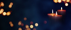 Candle lights in blue darkness with golden bokeh for solemn moments