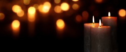 Candle lights in darkness with golden light effects and bokeh for solemn moments