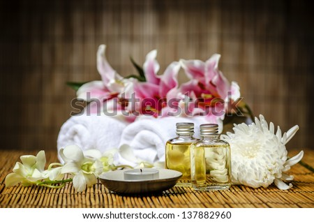 Candle, massage oil, white towels prepared for spa & massage