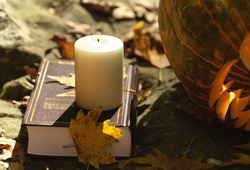 Candle on book and carved pumpkin on autumn foliage on nature background. Reading books about Halloween concept.