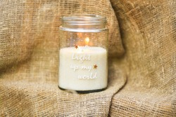Candle. One large candle lit stands on a sackcloth with the inscription: You Light up my world.