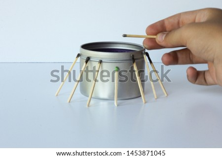 candle with burned matches surrounding a non-lit match.
