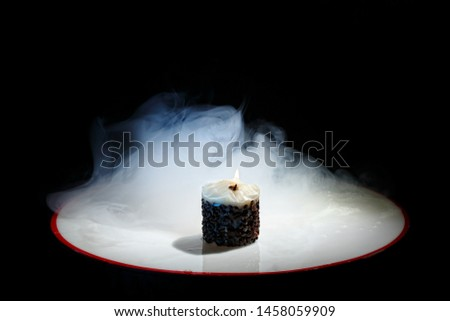 Candle with flame and jets of smoke on a black background. Original candle with fire in the blue smoke. Beautiful background. Coffee. Coffee grains on a candle. Beautiful wallpaper. Contemporary art.