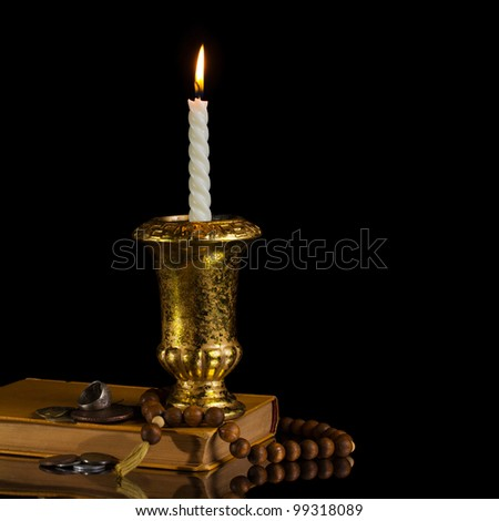 Candle with rosary, antique book and coins