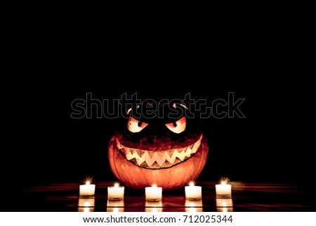 Candlelight halloween pumpkin smile with burning fire eyes mouth. Big spooky helloween symbol has a glowing mad face and smiling with sharp teeth and bad look. Black orange nightmare of October 31st