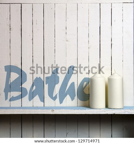 "Candles against rustic bathroom wall; wall is stencilled with the word ""Bathe"""