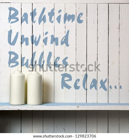 """Candles against rustic bathroom wall; wall is stencilled with the words """"Bathtime, Unwind, Bubbles, Relax."""""""