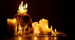 Candles and human skull in darkness close up
