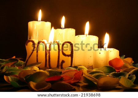 candles and petals in black background with warm light