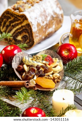 Candles, apples, dried fruits, fir branches and poppy seed cake on christmas eve table