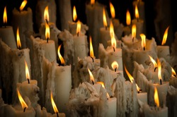 Candles are burning for believe or hope in Lourdes, France.