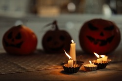 candles are burning on the table. Halloween pumpkin lantern with scary face on background. Family preparing all hallows eve Halloween party decorations. Background, copy space. selective focus.