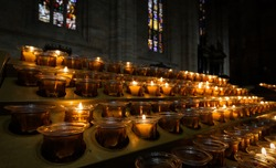 Candles burn inside church, close view of candles in dark cathedral interior. Concept of faith, prayer and worship.
