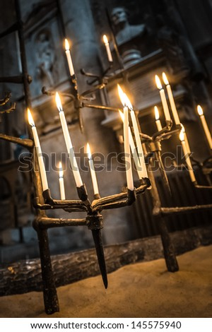candles burning in a dark gothic building