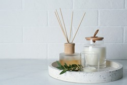 Candles, eucalyptus branch and aromatic reed air freshener on white table near brick wall, space for text. Interior elements