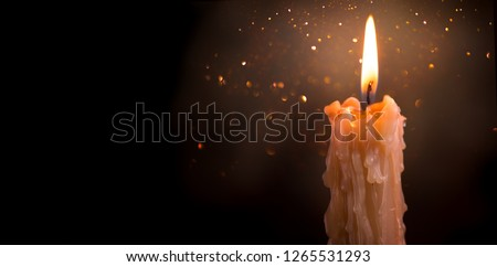 Photo of  Candles flame close up on a dark background. Candle light border design. Melted Wax Candles Burning at Night. White Candles Burning in the Dark. Candlelight. Widescreen