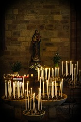 Candles in a church, Virgin Mary holding Jesus statue in the background
