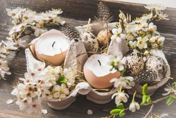 Candles in eggshells, quail eggs and white blossoming apple tree branches on a wooden tray as an Easter decoration