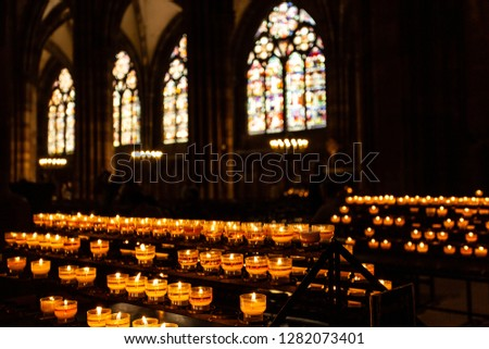 Candles in the Catholic Church. Windows with the sunlight on the background.