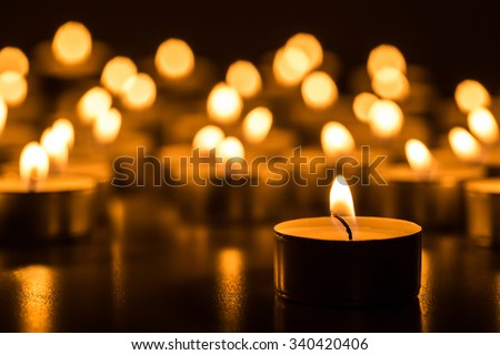 Candles light. Christmas candles burning at night. Abstract candles background. Golden light of candle flame.