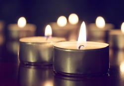 Candles lights on dark background. Light of candle flame, holiday background.Many burning candles.