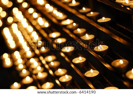 Candles of faith - rows of candles glowing in a dark church