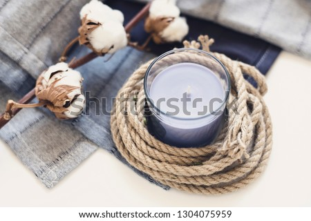 Candles on a gentle blue blanket with cotton branches #1304075959