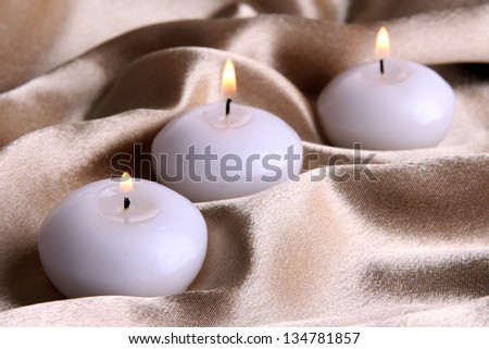Candles on golden fabric close-up