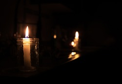 Candles on kitchen counter during power outage. 2 candles are inside a mason jar. Pitch black room except the candle lights. Selective focus on first candle with bokeh lights in the back.