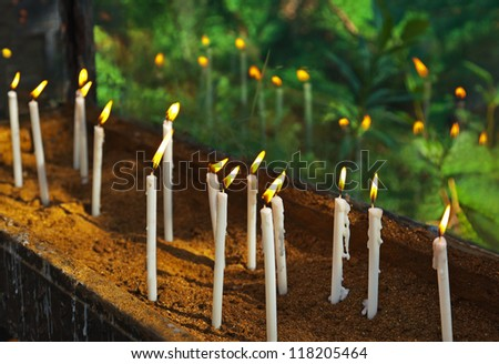 Candles on tomb at cemetery - religion background