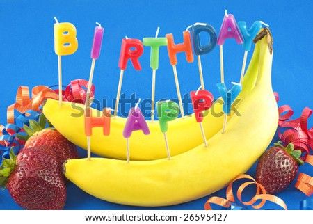 Candles spelling Happy Birthday stuck in bananas instead of cake for healthy lifestyle birthday, blue background with copy space