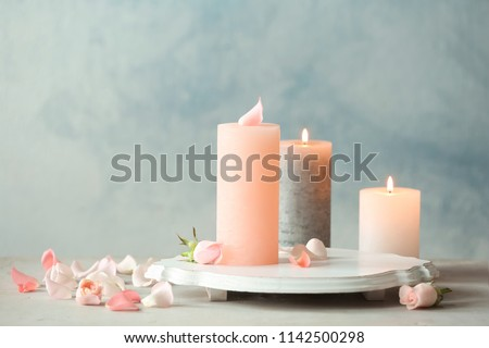 Candles with floral decor on table against color background #1142500298