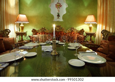 candlestick with candle at glass table with serving, lamps and sofas in luxury restaurant