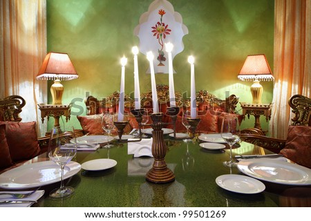 candlestick with five candles at glass table with serving, lamps and sofas in luxury restaurant