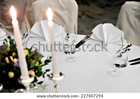 Candlestick with lit candles and floral arrangement on elegant dinner table