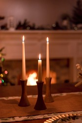 Candlesticks glowing on the table in front of the fireplace at Christmastime