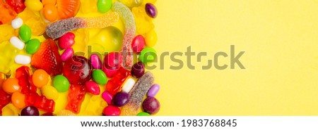Candy assorted banner copy space. Candy layout on a yellow background . Copy space candy. An article about sweets. Marmalade candies. The decor of a candy store. Yellow background
