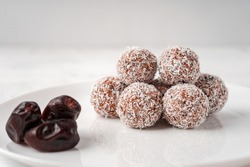 Candy balls made of dates and coconut shavings in a white dish on a light background near the dates.