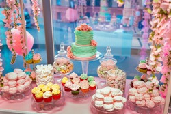Candy Bar in pinky colors. Delicious sweet buffet with cupcakes and wedding cake. Sweet holiday buffet with marshmallows and other desserts.