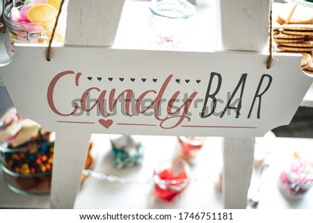 Candy bar lettering on white stand. Various sweets and gummy candies in background. Celebration, party, birthday or wedding concept.