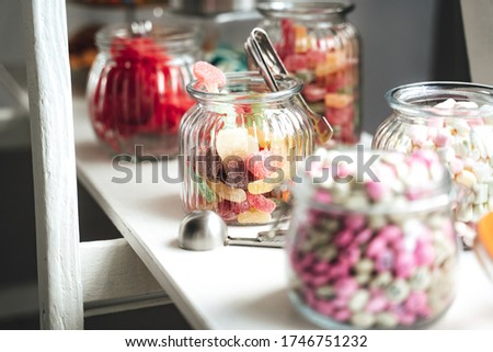 Candy bar of several kinds of colorful candies in glass jars laying on white shelf. Wedding or party concept.