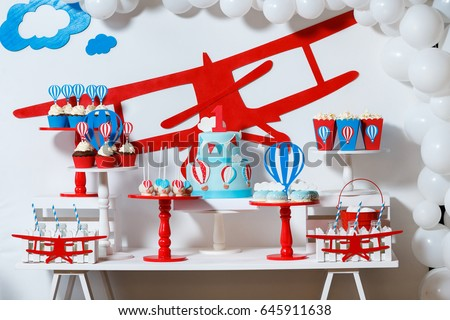 Candy bar on boy's birthday party with a lot of different candies, popcorn, beverages and big cake. Decorated in blue,red and white colors, balloons or aviation theme, indoor